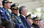 Colombia's Interim Defense Minister and Commander of the Armed Forces Gen. Luis Fernando Navarro, second from left, sits with Colombia's President Ivan Duque, center, during a graduation ceremony for police cadets in Bogota, Colombia, Thursday, Nov. 7, 2019. Colombia's Defense Minister Guillermo Botero resigned Wednesday after a lawmaker accused him of failing to disclose that eight minors had been killed in a military operation against dissident rebels. (AP Photo/Fernando Vergara)