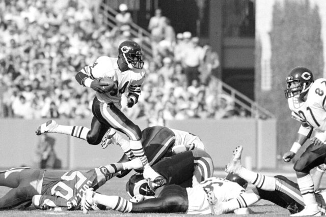 FILE - In this Nov. 11, 1984, file photo, Chicago Bears running back Walter Payton (34) leaps over Los Angeles Rams linebacker Jim Collins (50) who manages to grab his leg during first half action in Anaheim, Calif. The Bears boast a record 28 Hall of Famers, from founder George Halas to 2018 inductee Brian Urlacher. But when it comes to the draft, the sweetest pick of all has to be Payton. (AP Photo/Reed Saxon)