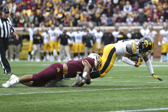 Iowa running back Ivory Kelly-Martin is tackled by Minnesota's defensive back Jacob Huff during an NCAA college football game Saturday, Oct. 6, 2018, in Minneapolis. (AP Photo/Stacy Bengs)