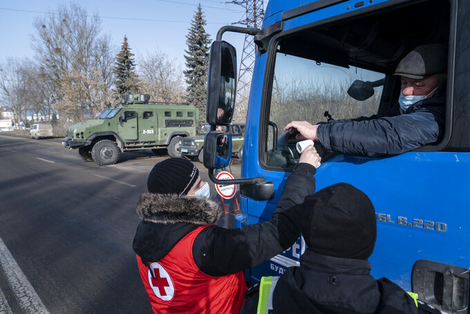 A medical worker checks the temperature of a driver at the checkpoint near Ivano-Frankivsk, Ukraine, Thursday, Feb. 25, 2021. Ukraine has recorded a 50% increase in the number of daily new coronavirus infections, as the country takes the first steps in its vaccination campaign. Health Minister Maxim Stepanov said Thursday that 8,417 new infections were found over the past day, up from 5,424 a day earlier. (AP Photo/Evgeniy Maloletka)