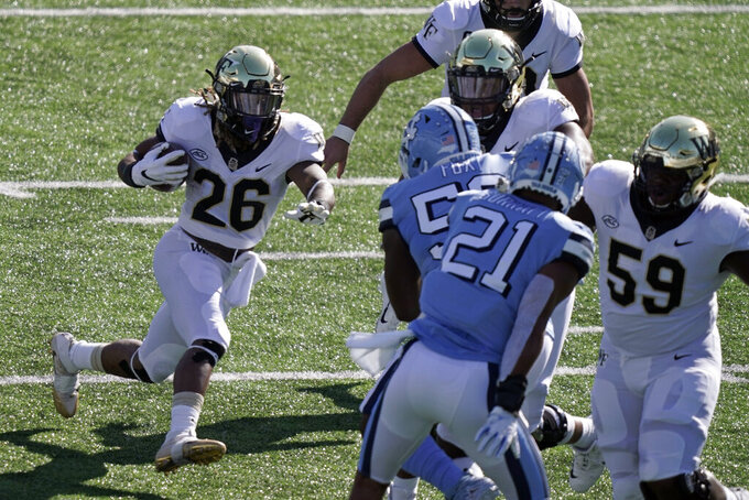 Wake Forest running back Christian Beal-Smith (26) runs against North Carolina during the first half of an NCAA college football game in Chapel Hill, N.C., Saturday, Nov. 14, 2020. (AP Photo/Gerry Broome)