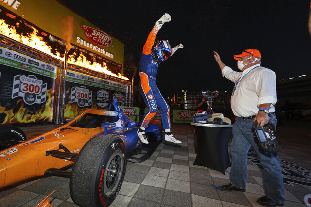 In this photo provided by Chris Owens/INDYCAR Series, Scott Dixon, left, jumps off his car toward team owner Chip Ganassi as the two celebrate Dixon's IndyCar auto race win at Texas Motor Speedway in Fort Worth, Texas, Saturday, June 6, 2020. (Chris Owens/INDYCAR Series via AP)