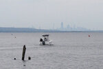 A boat heads out into Raritan Bay in Keyport, N.J., Tuesday, April 19, 2021, with the New York City skyline on the horizon. A Massachusetts company wants to build a high-voltage power line that would come ashore in Keyport and connect electricity from a future wind farm off the New Jersey coast to the onshore electrical grid. (AP Photo/Wayne Parry)