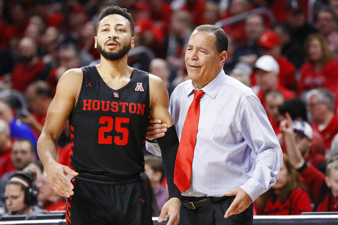 Houston head coach Kelvin Sampson, right, speaks with Galen Robinson Jr. (25) in the first half of an NCAA college basketball game against Cincinnati, Sunday, March 10, 2019, in Cincinnati. (AP Photo/John Minchillo)