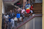 In this March 27, 2020, photo, residents of the densely populated Hillbrow neighborhood of downtown Johannesburg, confined in an attempt to prevent the spread coronavirus, stand on a staircase. South Africa went into a nationwide lockdown for 21 days in an effort to mitigate the spread to the coronavirus. (AP Photo/Jerome Delay)