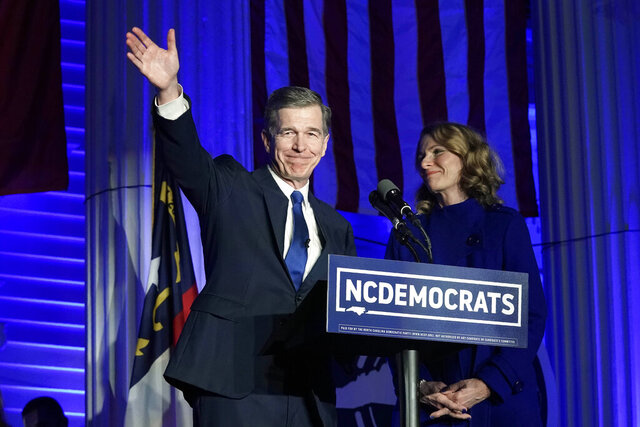 North Carolina Gov. Roy Cooper, joined by his wife Kristin, reacts after being declared winner over Republican Dan Forest in the governor's race in Raleigh, N.C., Tuesday, Nov. 3, 2020. (AP Photo/Gerry Broome)