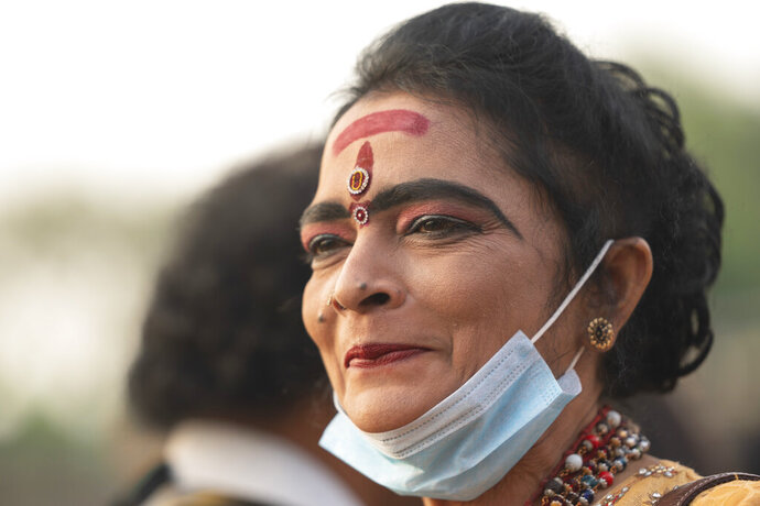 In this Feb. 8, 2020, photo, a Hindu devotee smiles as she lowers down her face mask during a procession at the Thaipusam festival at Batu Caves in Selangor, Malaysia. Tens of thousands of ethnic Hindus, meanwhile, gathered last weekend to celebrate the annual festival, undeterred by the outbreak of a new virus. (AP Photo/Vincent Thian)