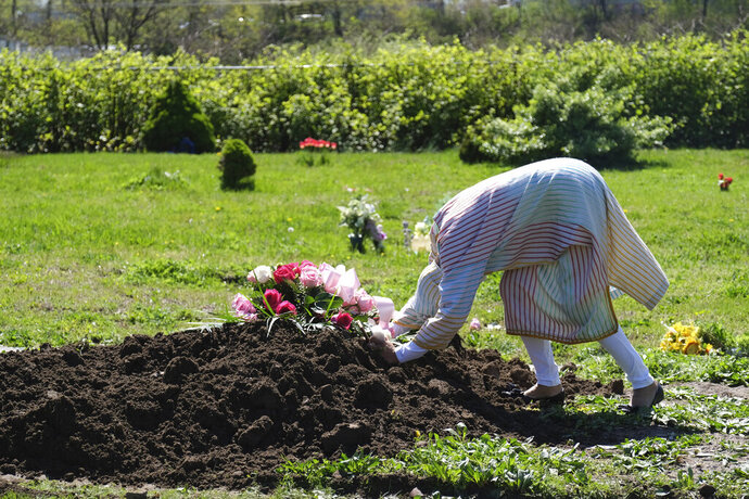Erika Bermudez becomes emotional as she leans over the grave of her mother Eudiana Smith after she was buried in Bayview Cemetery Saturday, May 2, 2020, in Jersey City, N.J., Bermudez was not allowed to approach the gravesite until after cemetery workers had buried her mother completely; other members of the family and friends stayed in their cars. (AP Photo/Seth Wenig)