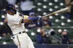 CORRECTS TO HITS AN INFIELD GROUND BALL TO DRIVE IN THE WINNING RUN - Milwaukee Brewers' Orlando Arcia hits an infield ground ball to drive in the winning run during the 10th inning of an opening day baseball game against the Minnesota Twins, Thursday, April 1, 2021, in Milwaukee. (AP Photo/Aaron Gash)