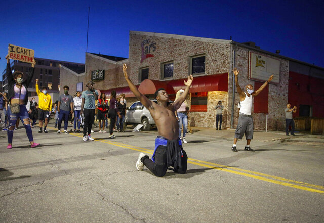 In this May 29, 2020, photo, Marcus Lavon of Des Moines raises his hands during a protest in Des Moines. Protests have been erupting all over the country after George Floyd died earlier this week in police custody in Minneapolis. (Bryon Houlgrave/The Des Moines Register via AP)