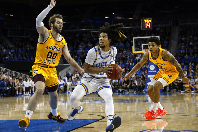 FILE - In this Thursday, Feb. 27, 2020, file photo, UCLA guard Tyger Campbell (10) drives between Arizona State forward Mickey Mitchell (00) and guard Rob Edwards (2) during an NCAA college basketball game, in Los Angeles. Campbell was the only player to start all 31 games during the 2019-20 season, averaging 8.3 points and five assists, most among the Pac-12's returners. (AP Photo/Ringo H.W. Chiu, File)