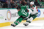 Dallas Stars center Radek Faksa (12) and Minnesota Wild defenseman Ryan Suter (20) give chase after a loose puck in the first period of an NHL hockey game in Dallas, Tuesday, Oct. 29, 2019. (AP Photo/Tony Gutierrez)