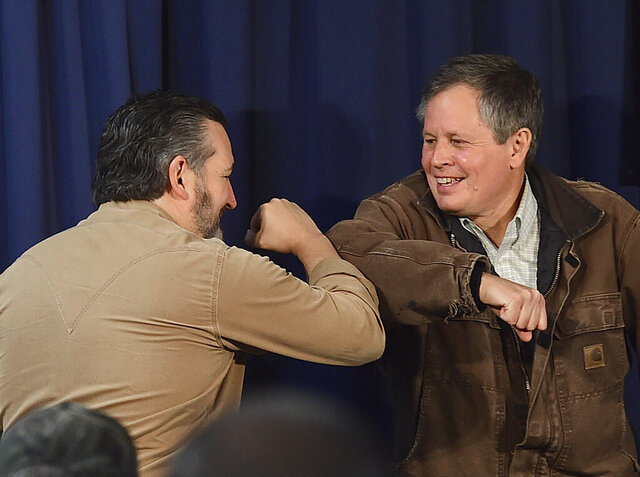 In this Thursday, Oct. 29, 2020, photo, Republican Senators, Ted Cruz, left, of Texas and Steve Daines of Montana, bump elbows during a campaign rally in Billings, Mont. Sen. Daines is being challenged in Tuesday's election by Montana Gov. Steve Bullock, a Democrat. (Larry Mayer/The Billings Gazette via AP)