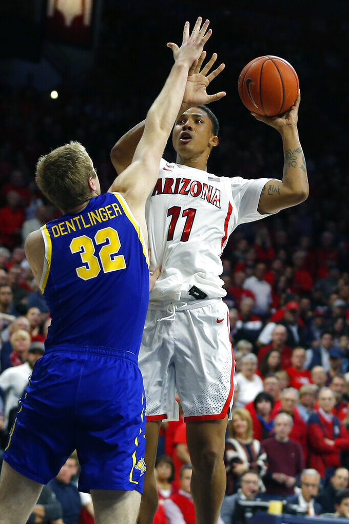 Arizona forward Ira Lee (11) shoots over South Dakota State forward Matt Dentlinger (32) in the second half during an NCAA college basketball game, Thursday, Nov. 21, 2019, in Tucson, Ariz. (AP Photo/Rick Scuteri)
