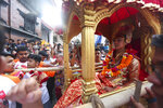 Devotees carry the chariot of living god Bhairabh during Indra Jatra festival, an eight-day festival that honors Indra, the Hindu god of rain, in Kathmandu, Nepal, Friday, Sept. 13, 2019. Families gather for feasts and at shrines to light incense for the dead, and men and boys in colorful masks and gowns representing Hindu deities dance to the beat of traditional music and devotees' drums, drawing tens of thousands of spectators to the city's old streets.  (AP Photo/Niranjan Shrestha)