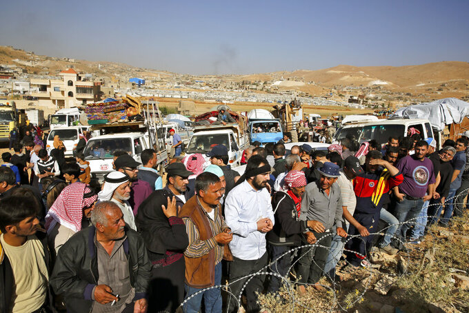 FILE - In this June 28, 2018 file photo, Syrian refugees gather in and near their vehicles getting ready to cross into Syria from the eastern Lebanese border town of Arsal, Lebanon.  A number of Syrian refugees who returned home have been subjected to detention, disappearance and torture at the hands of Syrian security forces, proving that it still isn't safe to return to any part of the country, Amnesty International said in a new report released Tuesday, Sept. 7, 2021. It documents what it said were violations committed by Syrian intelligence officers against some returnees, including 13 children between mid-2017 and spring 2021. (AP Photo/Bilal Hussein, File)
