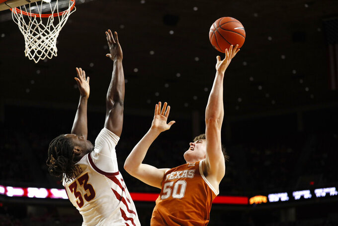 Texas center Will Baker (50) shoots over Iowa State forward Solomon Young, left, during the second half of an NCAA college basketball game, Saturday, Feb. 15, 2020, in Ames, Iowa. (AP Photo/Charlie Neibergall)