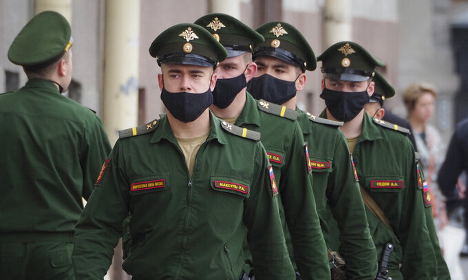 Russian soldiers, a guard team wearing face masks to protect against coronavirus infection walk from their barracks to a military headquarters in St.Petersburg, Russia, Thursday, June 11, 2020. (AP Photo/Dmitri Lovetsky)