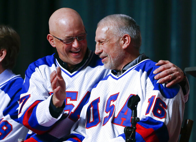 "FILE - In this Feb. 21, 2015, file photo, Jack O'Callahan, left, and Mark Pavelich of the 1980 U.S. ice hockey team talk during a ""Relive the Miracle"" reunion at Herb Brooks Arena in Lake Placid, N.Y. Pavelich has died at a treatment center for mental illness. Officials in Anoka County, Minnesota, confirmed Friday, March 5, 2021, that Pavelich, 63, died at the Eagle's Healing Nest in Sauk Centre, Minn., Thursday morning. The cause and manner of death are still pending. (AP Photo/Mike Groll, File)"