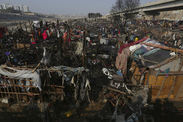 CAPTION CORRECTION: CORRECTS YEAR: Dwellers collect their belongings following a fire that gutted homes in Karachi, Pakistan, Wednesday, Jan. 22, 2020. Hundreds of huts were burnt to ashes as fire erupted making dozens of families homeless in a slum of Karachi, local media reported. (AP Photo/Fareed Khan)