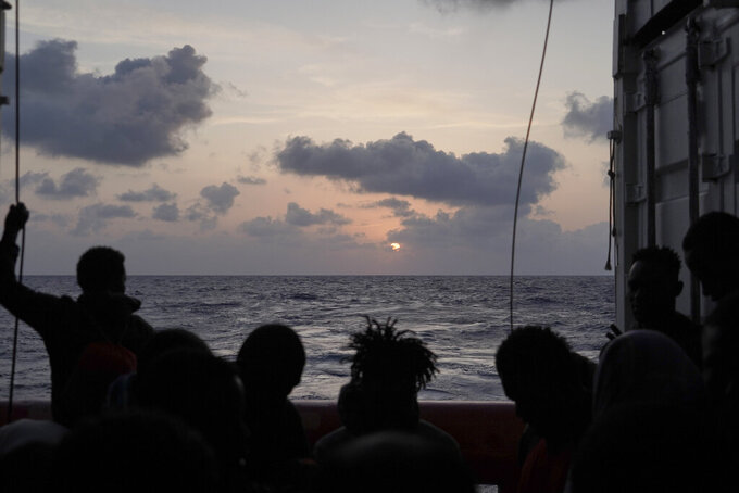 FILE - In this Saturday, Sept. 21, 2019 file photo, migrants are silhouetted during the sunrise on the deck of the Ocean Viking as it sails in the Mediterranean Sea. A rescue ship with 422 migrants aboard, some of whom tested positive for COVID-19, is heading to Sicily. SOS Mediterranee, the humanitarian group which operates the rescue ship Ocean Viking, told The AP on Sunday, Feb. 7, 2021 that Italy granted the vessel permission to enter the port of Augusta. (AP Photo/Renata Brito)