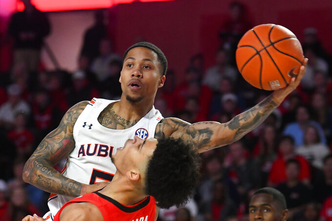 Auburn guard J'Von McCormick looks to pass over the head of Georgia forward Toumani Camara during the first half of an NCAA college basketball game Wednesday, Feb. 19, 2020, in Athens, Ga. (AP Photo/John Amis)