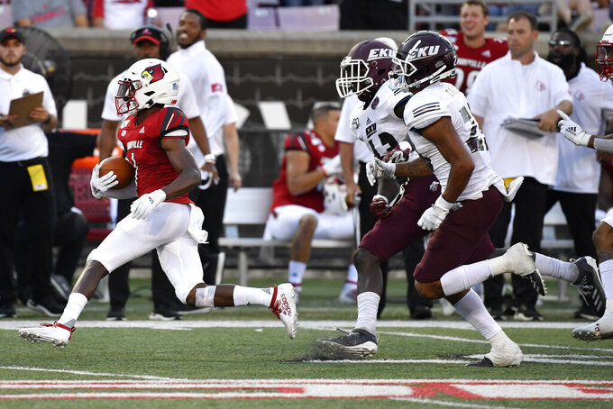 Louisville wide receiver Tutu Atwell (1) is pursued by Eastern Kentucky defensive back Joseph Sayles (43) and wide receiver Alex Cabrera (23) during the first half of an NCAA college football game in Louisville, Ky., Saturday, Sept. 7, 2019. (AP Photo/Timothy D. Easley)