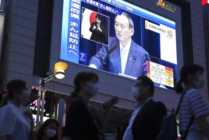 FILE - In this June 17, 2021, file photo, people walk past a big screen as Japanese Prime Minister Yoshihide Suga holds a news conference in a live broadcasting on the current state of Japan's response to the coronavirus, in Tokyo. A state of emergency began Monday, July 12, 2021 in Tokyo, as the number of new cases is climbing fast and hospital beds are starting to fill just 11 days ahead of the Tokyo Olympics. (AP Photo/Eugene Hoshiko, File)