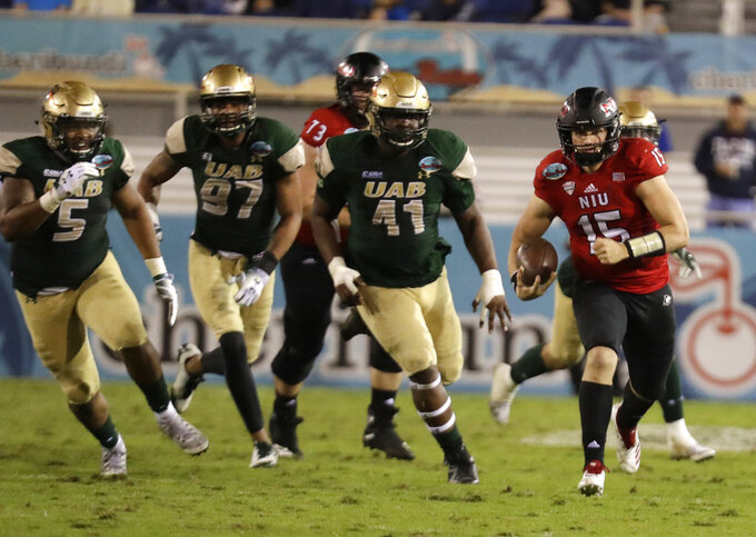 Northern Illinois quarterback Marcus Childers (15) runs for a first down as UAB defensive lineman Zachary Williams (5), defensive lineman Stacy Keely (97) and defensive lineman Quindarius Thagard (41) pursue during the second half of the Boca Raton Bowl NCAA college football game, Tuesday, Dec. 18, 2018, in Boca Raton, Fla. UAB won 37-13. (AP Photo/Lynne Sladky)