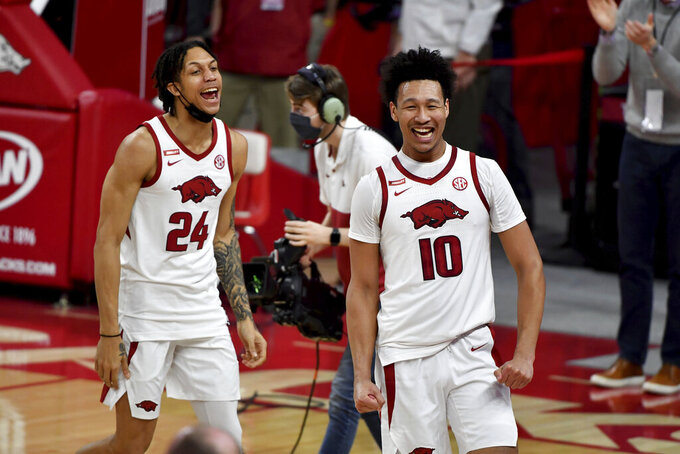 Arkansas forward Ethan Henderson (24) and Arkansas forward Jaylin Williams (10) celebrate after beating Alabama 81-66 during the second half of an NCAA college basketball game in Fayetteville, Ark. Wednesday, Feb. 24, 2021. (AP Photo/Michael Woods)