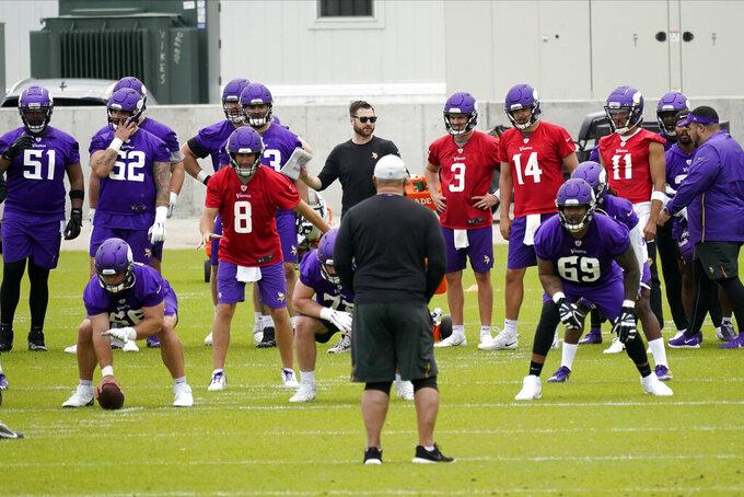 Minnesota Vikings players led by quarterback Kirk Cousins (8) go through offensive drills during NFL football practice in Eagan, Minn., Wednesday, June 2, 2021.(AP Photo/Jim Mone)