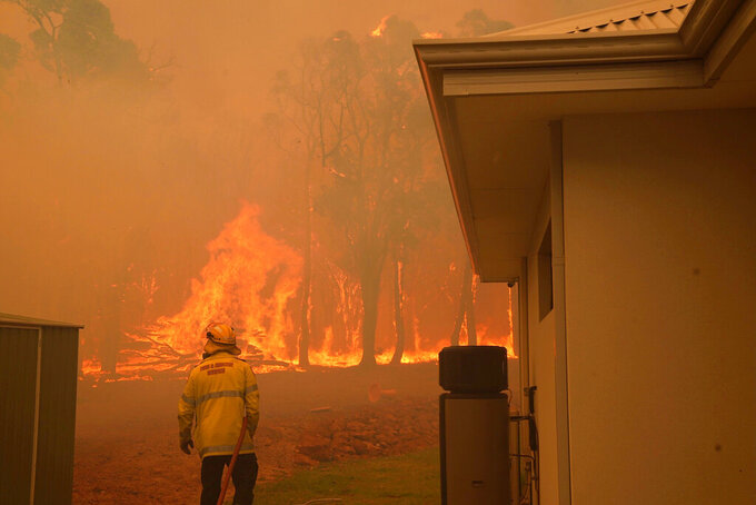 In this photo provided by Department of Fire and Emergency Services, a firefighter works at a fire near Wooroloo, northeast of Perth, Australia, Tuesday, Feb. 2, 2021. An out-of-control wildfire burning northeast of the Australian west coast city of Perth has destroyed dozens of homes and was threatening more. (Evan Collis/DFES via AP)