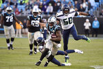 Carolina Panthers wide receiver D.J. Moore (12) runs the ball while Seattle Seahawks outside linebacker K.J. Wright (50) and cornerback Tre Flowers (21) chase during the second half of an NFL football game in Charlotte, N.C., Sunday, Dec. 15, 2019. (AP Photo/Mike McCarn)