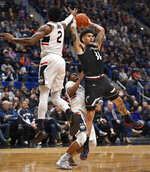 Cincinnati's Jarron Cumberland (34) passes under pressure from Connecticut's Tarin Smith (2) and Alterique Gilbert (3) during the second half of an NCAA college basketball game, Sunday, Feb. 24, 2019, in Hartford, Conn. (AP Photo/Jessica Hill)