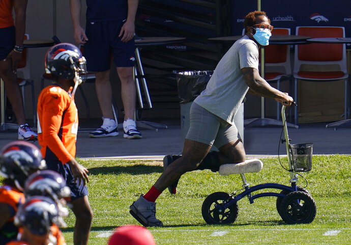 Injured Denver Broncos outside linebacker Von Miller uses a scooter to maneuver around as his teammates warm up before taking part in drills during an NFL football practice Wednesday, Oct. 14, 2020, at the team's headquarters in Englewood, Colo. (AP Photo/David Zalubowski)