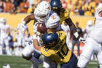 Texas running back Roschon Johnson (2) is tackled by West Virginia linebacker Dylan Tonkery (10) during the first half of an NCAA college football game Saturday, Oct. 5, 2019, in Morgantown, W.Va. (AP Photo/Raymond Thompson)