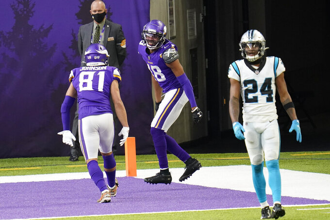 Minnesota Vikings wide receiver Justin Jefferson, center, celebrates with teammate Bisi Johnson (81) in front of Carolina Panthers cornerback Rasul Douglas (24) after catching a 10-yard touchdown pass during the second half of an NFL football game, Sunday, Nov. 29, 2020, in Minneapolis. (AP Photo/Jim Mone)