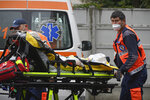 Paramedics bring an elderly patient to the emergency room, turned into a CODIV-19 unit due the high number of cases, at the Bagdasar-Arseni hospital in Bucharest, Romania, Tuesday, Oct. 12, 2021. Romania reported on Tuesday nearly 17,000 new COVID-19 infections and 442 deaths, the highest number of coronavirus infections and deaths in a day since the pandemic started, as the nation's health care systemstruggles to cope with an acute surge of new cases.(AP Photo/Andreea Alexandru)
