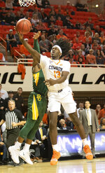 Oklahoma State guard Isaac Likekele (13) takes a shot under pressure from Baylor guard Devonte Bandoo (2) during an NCAA college basketball game in Stillwater, Okla., Saturday, Jan. 18, 2020. (AP Photo/Brody Schmidt)
