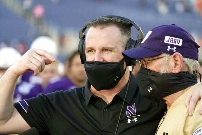 Northwestern head coach Pat Fitzgerald, left, celebrates with defensive coordinator Mike Hankwitz after winning the Citrus Bowl NCAA college football game against Auburn, Friday, Jan. 1, 2021, in Orlando, Fla. Northwestern beat Auburn 35-19. (AP Photo/John Raoux)
