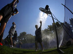 FILE - In this Tuesday, Aug. 1, 2017 file photo, a fan attending a Seattle Seahawks NFL football training camp reaches toward a fan as he cools off at a misting station in Renton, Wash., as temperatures rise in the Northwest. (AP Photo/Ted S. Warren, File)