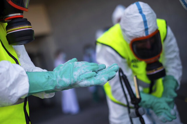 Spanish Royal Guard soldiers during disinfection work at a hospital to prevent the spread of the new coronavirus in Madrid, Spain, Sunday, March 29, 2020. Spain and Italy demanded more European help as they fight still-surging coronavirus infections amid the continent's worst crisis since World War II. The new coronavirus causes mild or moderate symptoms for most people, but for some, especially older adults and people with existing health problems, it can cause more severe illness or death. (AP Photo/Bernat Armangue)