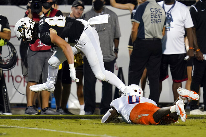 Central Florida tight end Alec Holler leaps over Boise State safety JL Skinner (0) on his way to a 23-yard touchdown reception during the first half of an NCAA college football game Thursday, Sept. 2, 2021, in Orlando, Fla. (AP Photo/John Raoux)