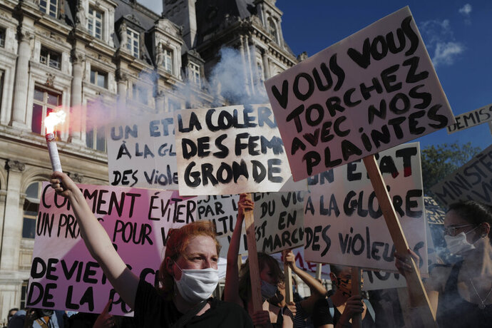 Women's rights activists protest against French President Emmanuel Macron's appointment of an interior minister who has been accused of rape and a justice minister who has criticized the #MeToo movement, in front of Paris city hall, in Paris, France, Friday, July 10, 2020. The French government said it remains committed to gender equality and defended the new ministers, stressing the presumption of innocence. Gerald Darmanin, Interior Minister, firmly denies the rape accusation, and an investigation is underway. New Justice Minister Eric Dupond-Moretti is a lawyer who has defended a government member accused of rape and sexual assault, and has ridiculed women speaking out thanks to the #MeToo movement. (AP Photo/Francois Mori)