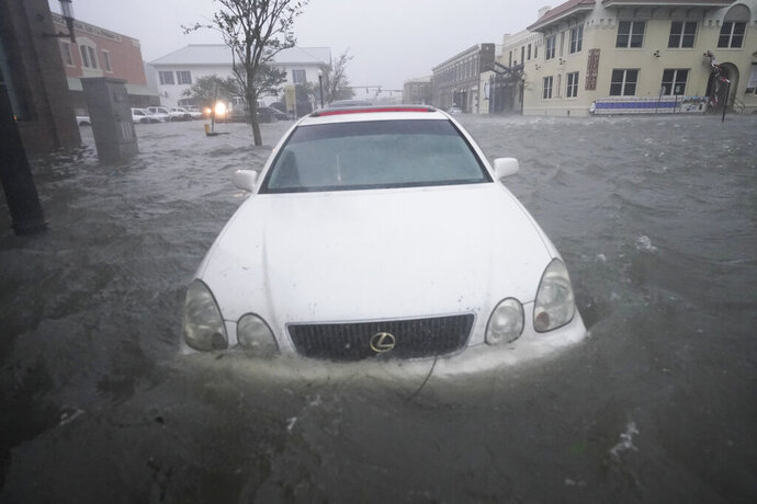 Flood waters move on the street, Wednesday, Sept. 16, 2020, in Pensacola, Fla. Hurricane Sally made landfall Wednesday near Gulf Shores, Alabama, as a Category 2 storm, pushing a surge of ocean water onto the coast and dumping torrential rain that forecasters said would cause dangerous flooding from the Florida Panhandle to Mississippi and well inland in the days ahead.(AP Photo/Gerald Herbert)