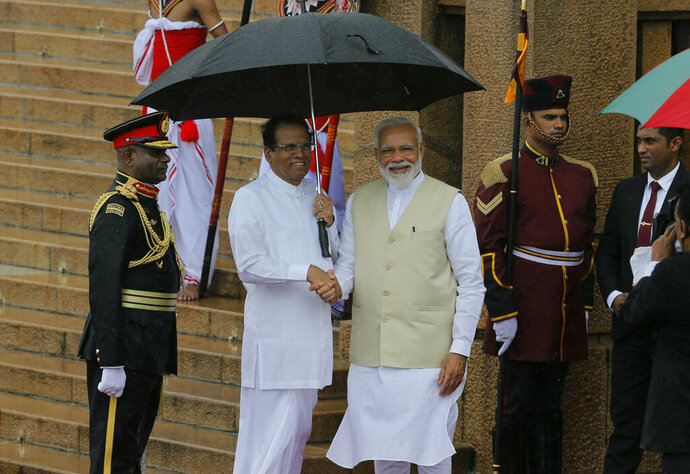 Indian Prime Minister Narendra Modi, center is received by the Sri Lankan President Maithripala Sirisena, center left, upon his arrival at the presidential secretariat in Colombo, Sri Lanka, Sunday, June 9, 2019. Modi arrived in Sri Lanka on Sunday for a brief visit as part of his first overseas tour since reelection that emphasizes India's