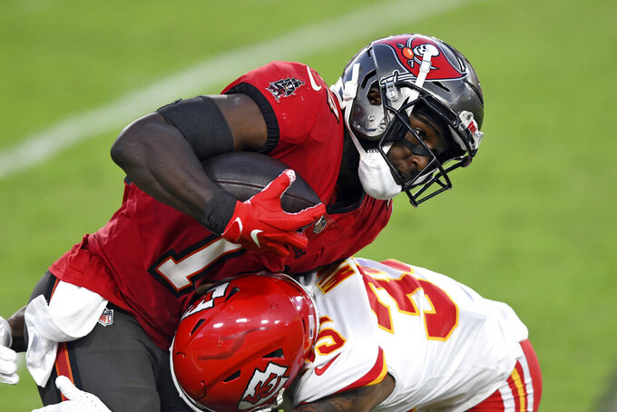 Tampa Bay Buccaneers wide receiver Chris Godwin (14) gets hit by Kansas City Chiefs cornerback Charvarius Ward (35) after a catch during the first half of an NFL football game Sunday, Nov. 29, 2020, in Tampa, Fla. (AP Photo/Jason Behnken)