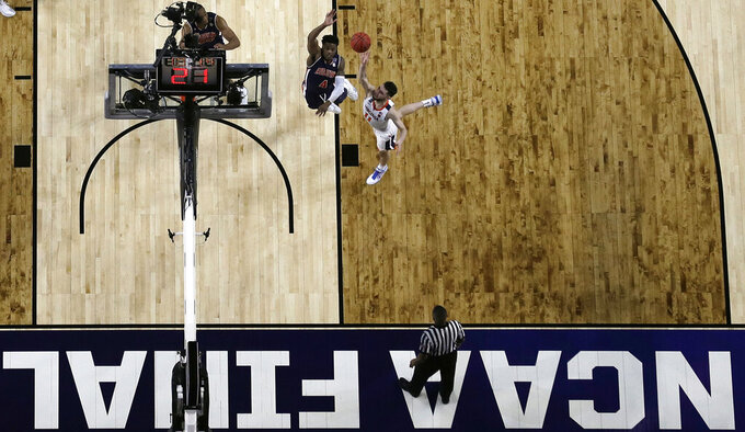 Virginia's Ty Jerome (11) takes a shot against Auburn's Malik Dunbar (4) during the first half in the semifinals of the Final Four NCAA college basketball tournament, Saturday, April 6, 2019, in Minneapolis. (AP Photo/Jeff Roberson)