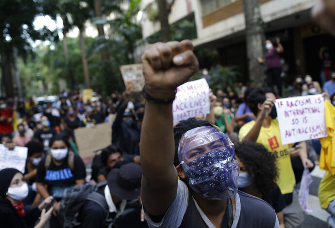 People protest against crimes committed by the police against black people in the favelas, outside the Rio de Janeiro's state government, Brazil, Sunday, May 31, 2020. The protest, called