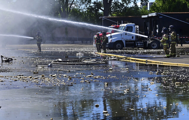 Firefighters attack a fire from the ground as several stations responded to a large fire at Metro Metals Recycling in St. Paul, Minn., on Tuesday, Aug. 18, 2020. (John Autey/Pioneer Press via AP)
